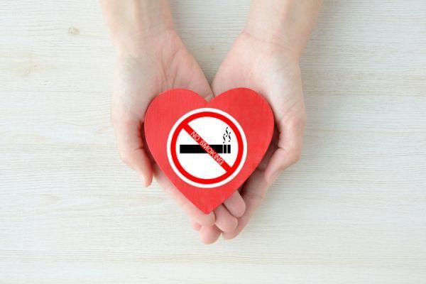 Manos mantienen pegatina corazon sin tabaco